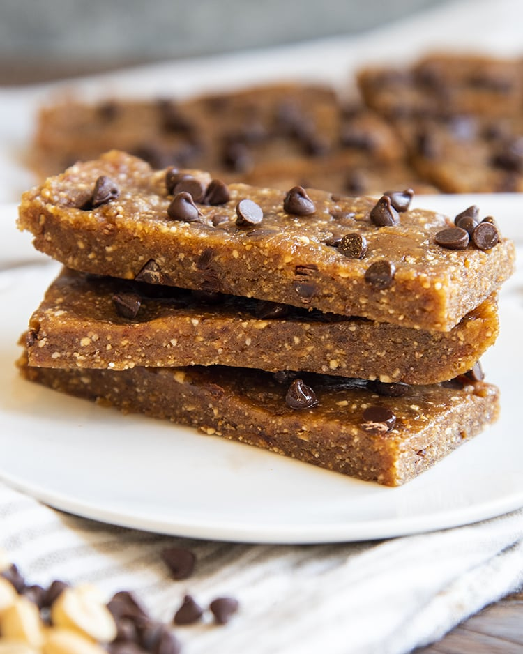 A stack of 3 homemade peanut butter chocolate chip larabars on a small plate with mini chocolate chips showing on the top one.