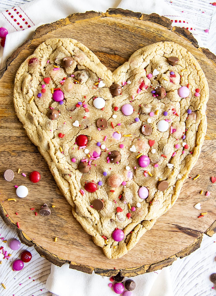 A big heart shaped cookie with valentine colored m&ms, chocolate chips, and valentine sprinkles set on a round wooden platter.