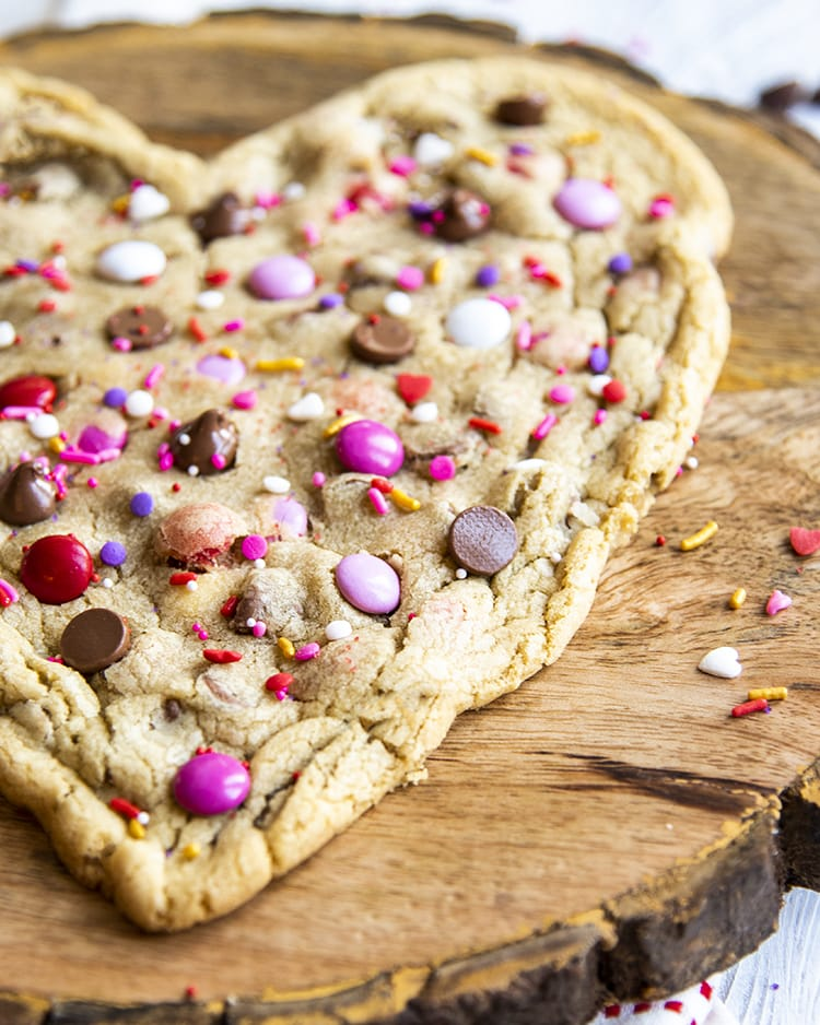 An angled close up of a corner of a heart shaped chocolate chip cookie. The cookie also is topped with valentine colored m&ms, and sprinkled with red, and white sprinkles.