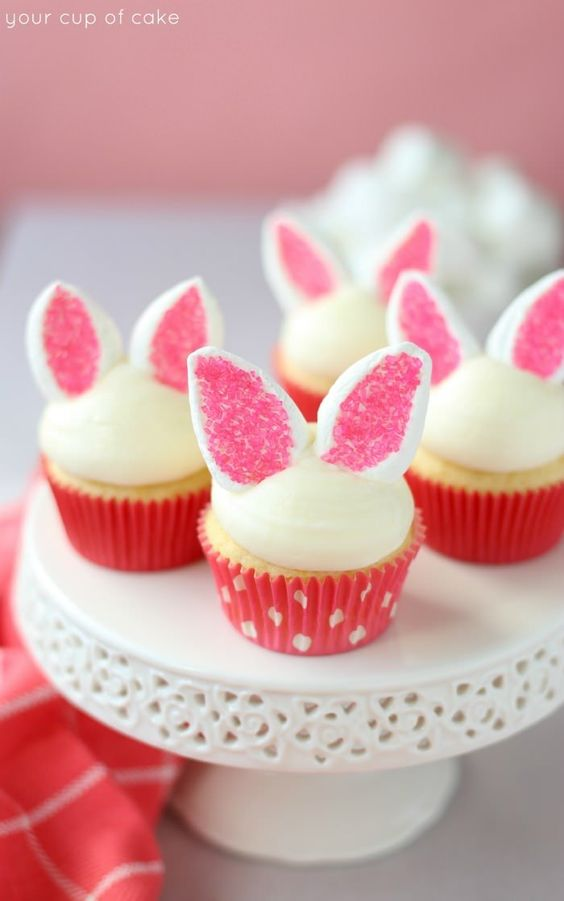 Four cupcakes on a cake stand with a half dome of white frosting and marshmallows cut in half and dipped in pink sprinkles to look like bunny ears on them.