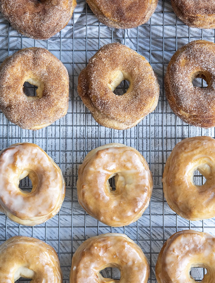 Cinnamon sugar and glazed donuts arranged in rows on a cooling rack.