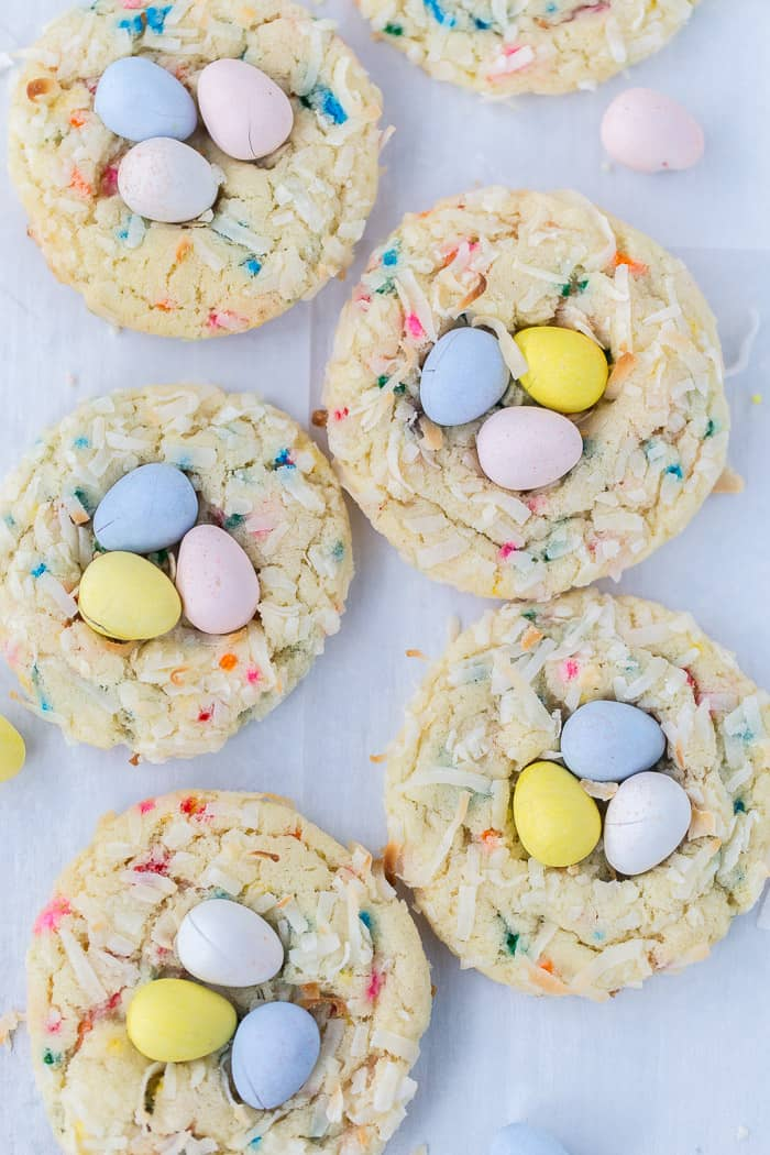 Cookies full of colored sprinkles, and covered in coconut, and topped with three pastel colored chocolate candies.