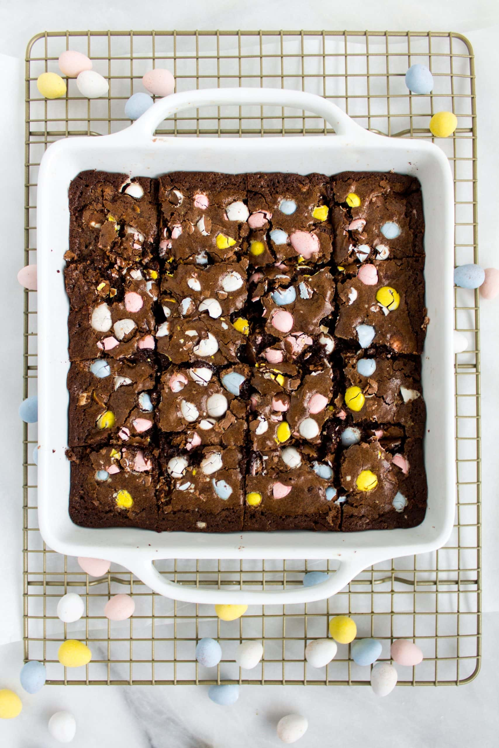 A square pan full of brownies that are full of chopped up cadbury mini eggs.