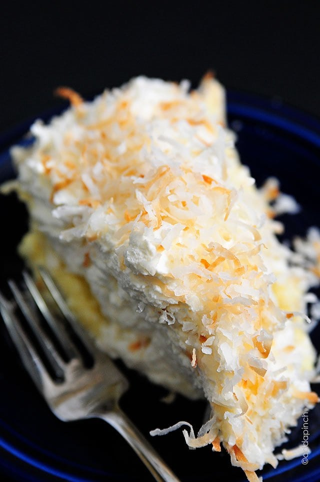 A close up of a slice of coconut cream pie on a blue plate topped with toasted coconut.