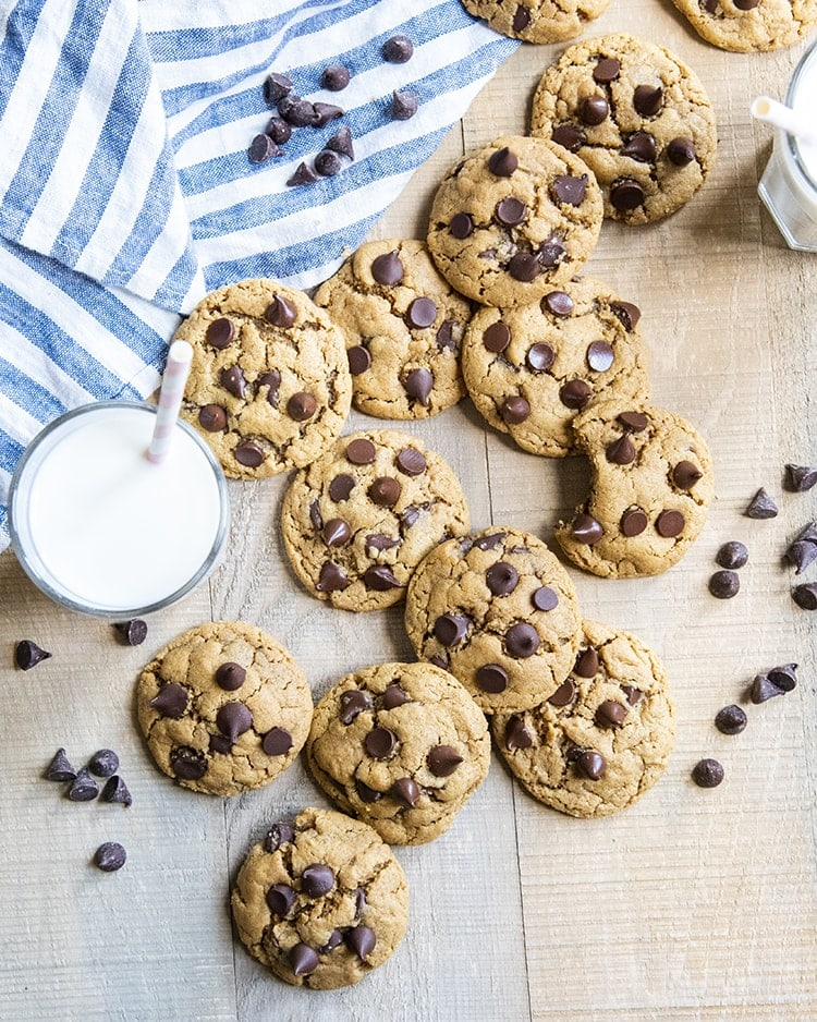 Flourless peanut butter chocolate chip cookies arranged randomly, slightly piled on a wooden surface, with a blue and white stripe cloth next to them. There is a glass of milk with a straw in it next to the cookies.