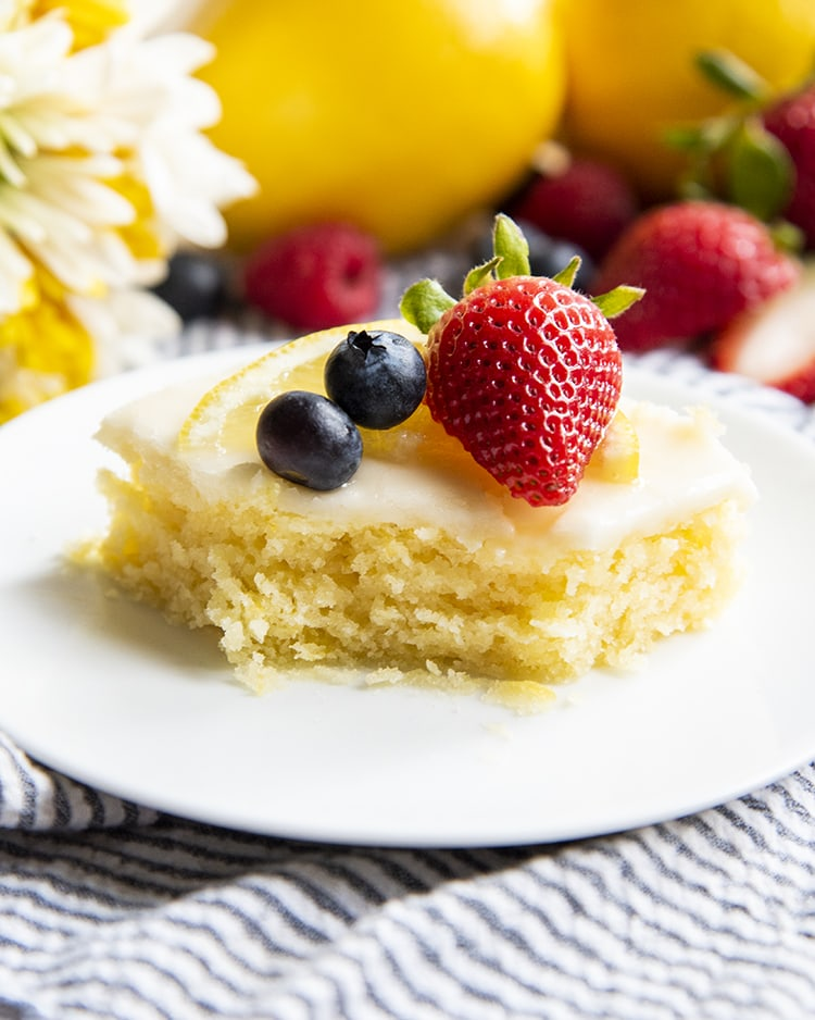 A slice of a yellow sheet cake on a plate that is topped with two blueberries, a strawberry, and lemon slice with a bite out of the front.