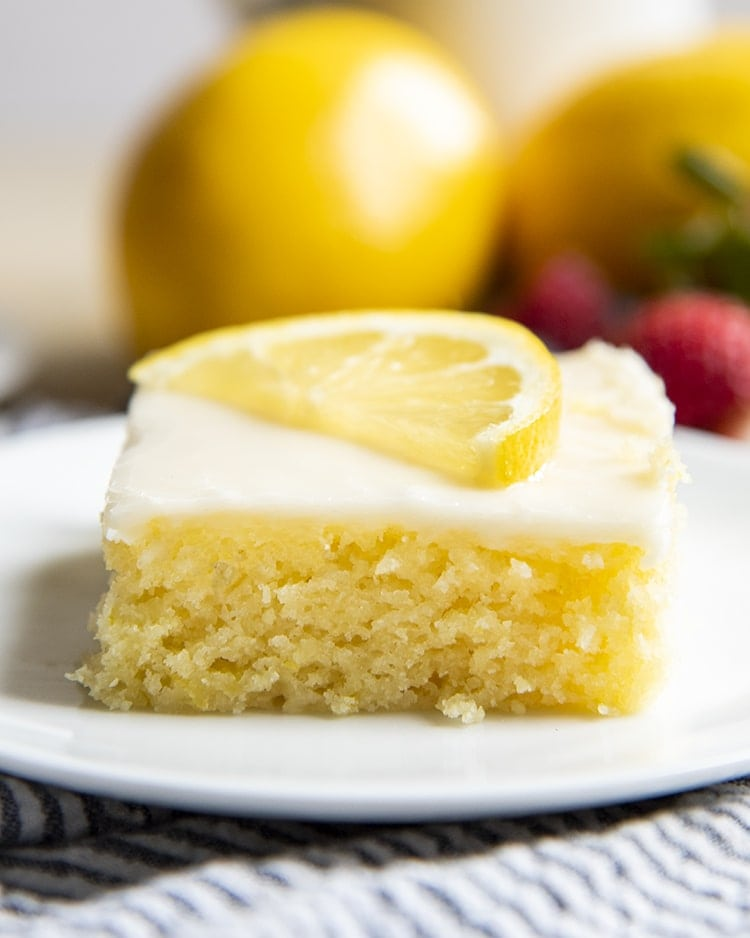 A close up of a slice of lemon sheet cake topped with a white icing, and a half slice of a lemon.