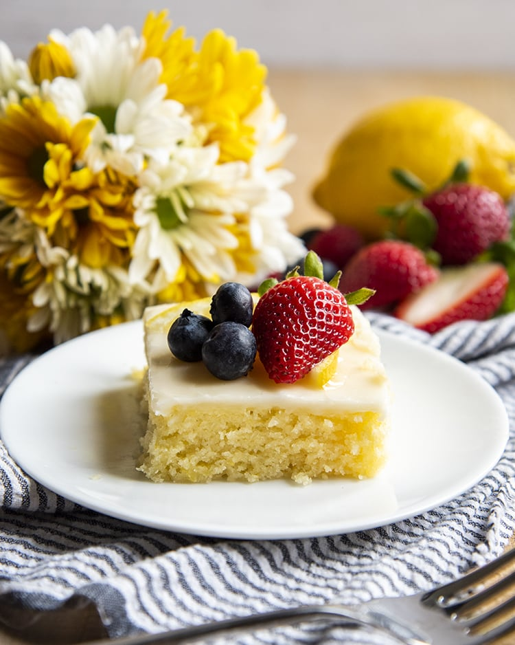 A slice of lemon sheet cake on a plate topped with fresh berries, and there are flowers behind the plate.
