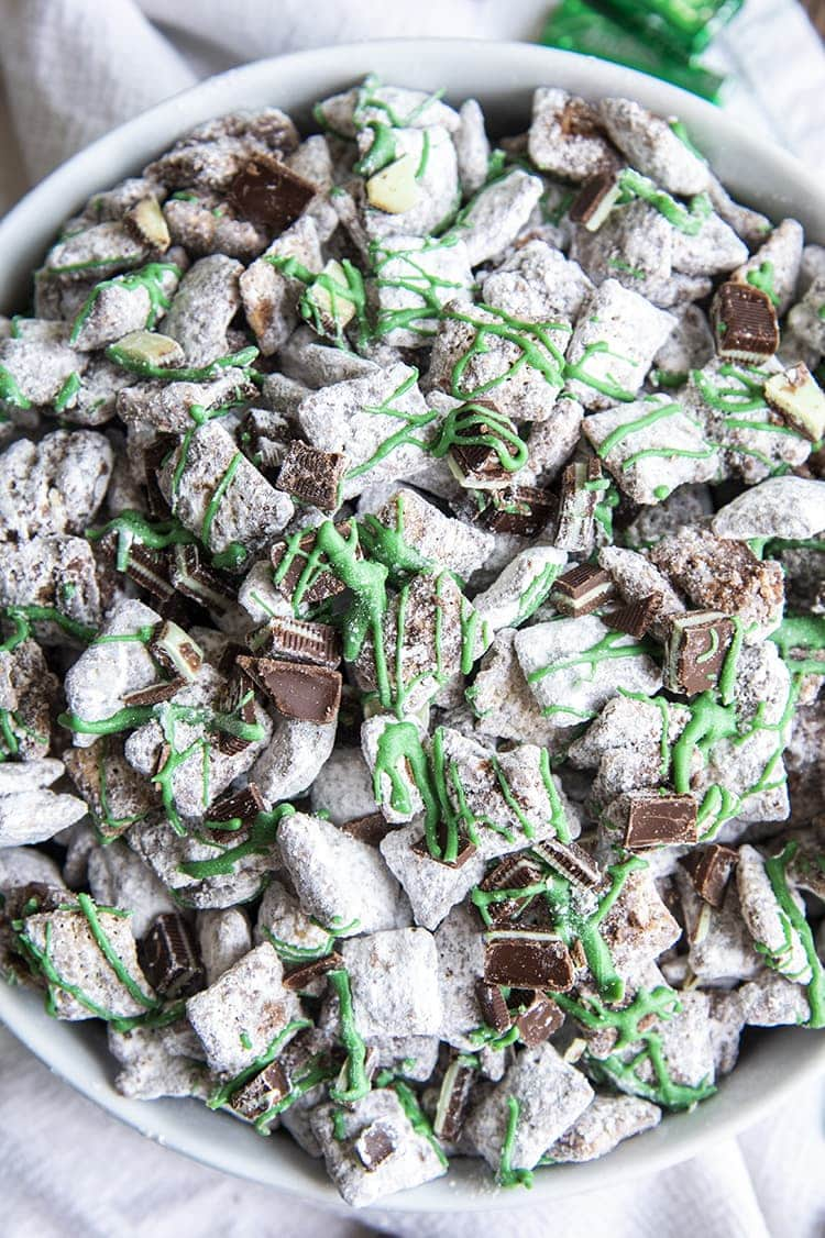 An overhead shot of mint muddy buddies in a white bowl. They are drizzled with green candy melts and there are chopped up Andes Mint pieces mixed in.