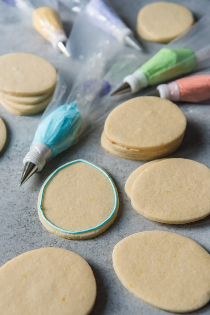 Sugar cookies shaped like Easter eggs, and one is decorated with a line of royal frosting on the outside.