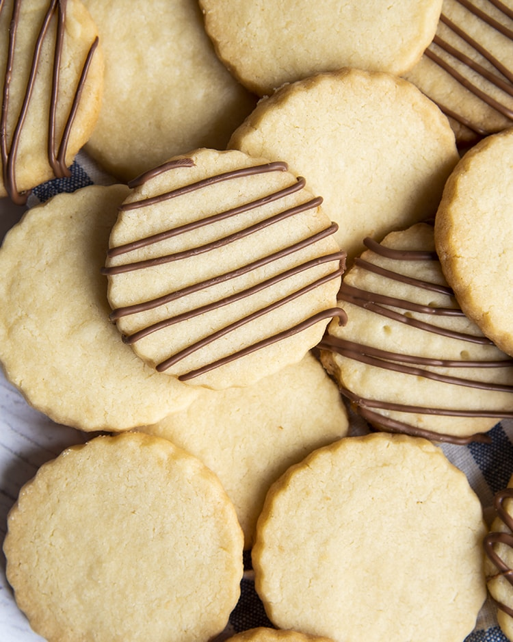 A close up of a pile of shortbread cookies, some of the cookies have chocolate drizzled over the top.