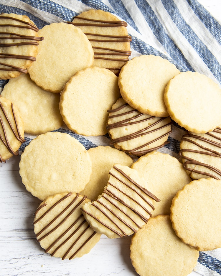 A pile of shortbread cookies, about half of them have chocolate drizzled thinly over the top.