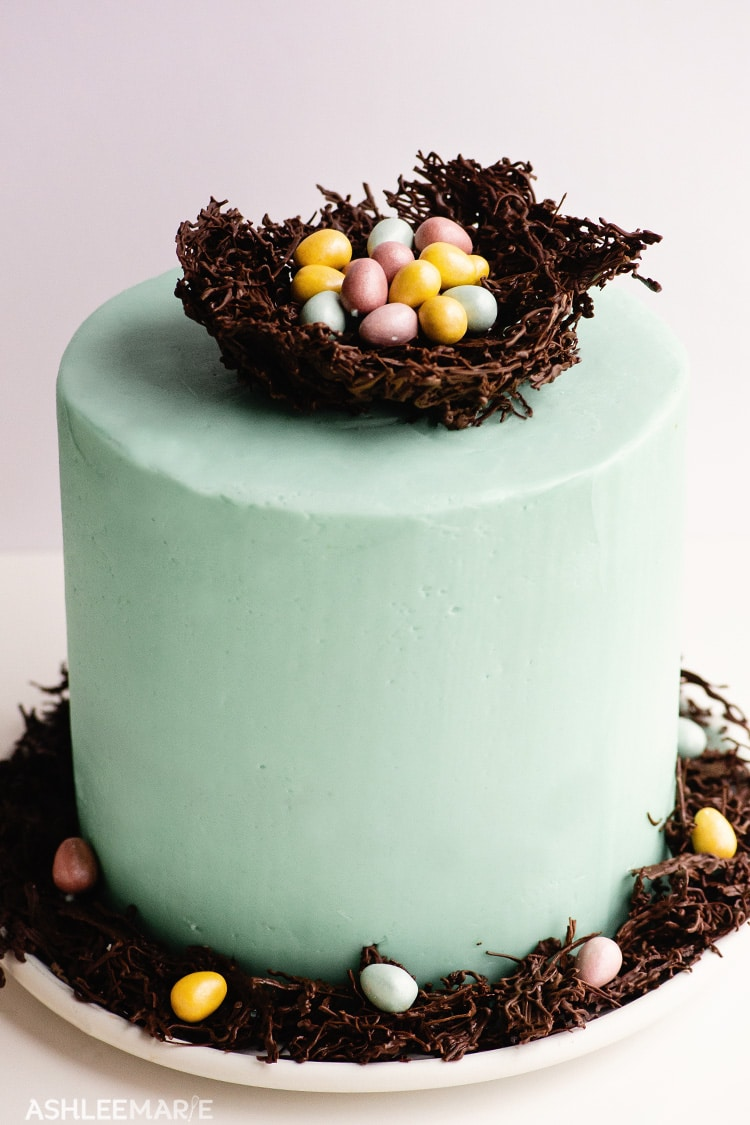 A light blue frosted cake topped with a chocolate nest, full of chocolate candy eggs.