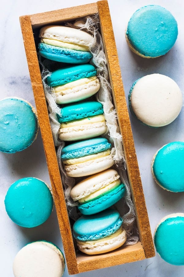 Macaroons in a box with a few on the sides. They have one half that is blue, and one half that is white and are filled with a white filling.