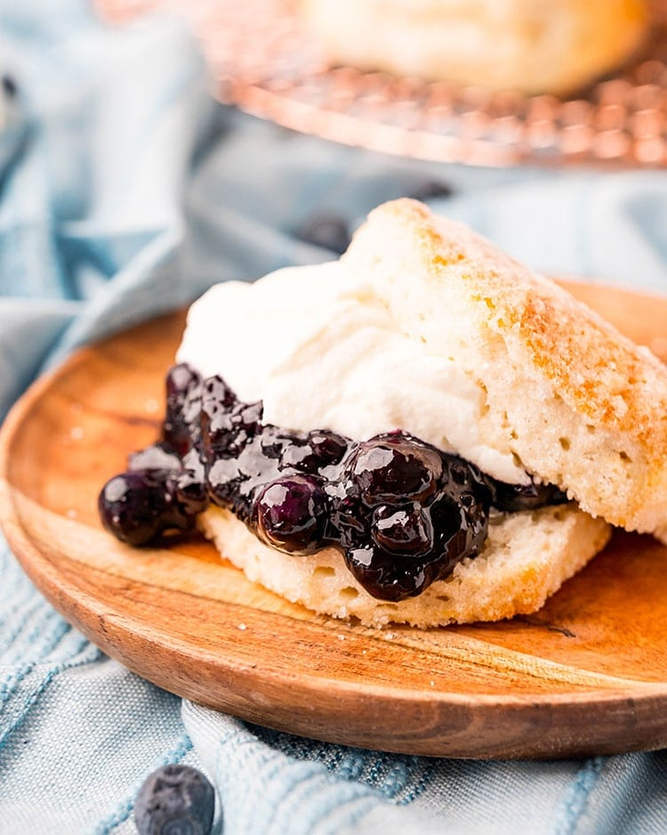 A wooden plate with a blueberry shortcake on top. There is a biscuit split in half with blueberry sauce, and whipped cream on top with the top biscuit half on top. The biscuit is coated in sugar.