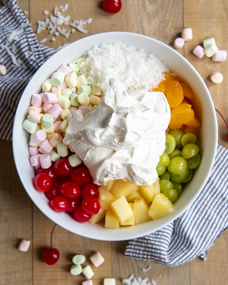 A white bowl full of the ingredients needed for ambrosia salad, separated. There is shredded coconut, mandarin oranges, green grapes, pineapple, maraschino cherries, and rainbow marshmallows. With a creamy whipped cream mixture in the middle.