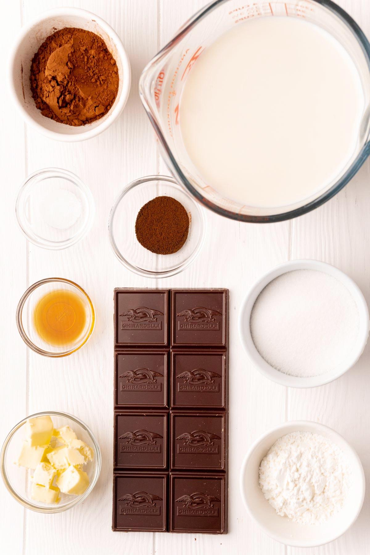 The ingredients needed to make chocolate pudding, cocoa powder, milk, sugar, vanilla, butter, cornstarch, espresso powder, and salt.
