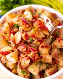 A close up of a bowl of warm german potato salad with red potatoes, bacon, and small pieces of red onion. There is a spoon in the bowl holding some of the salad.