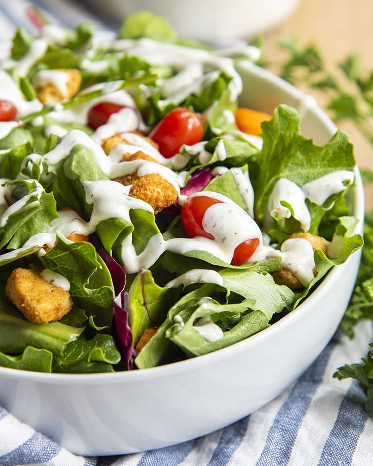 A white bowl full of salad topped with carrots, baby tomatoes, and croutons, and drizzled with ranch dressing.