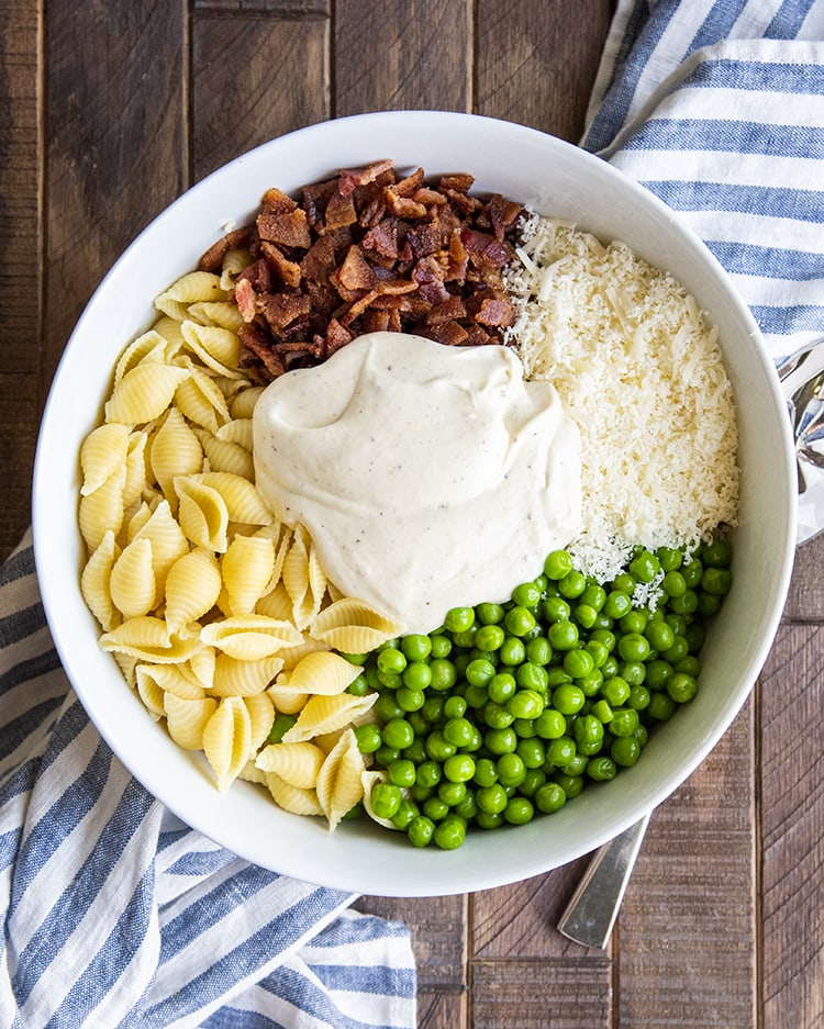 The ingredients needed to make creamy pasta salad, medium shells, crumbled bacon, grated parmesan, peas, and in the middle the white sauce.