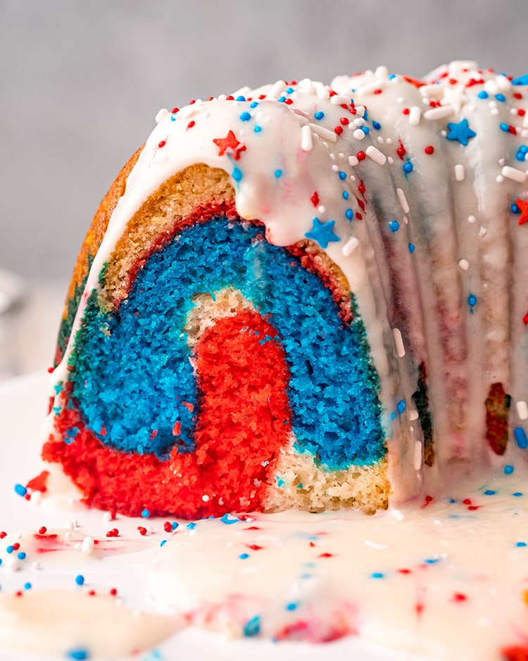 A cut of a patriotic bundt cake that is showing the red, white, and blue colors topped with a white glaze, and red, white, and blue sprinkles.
