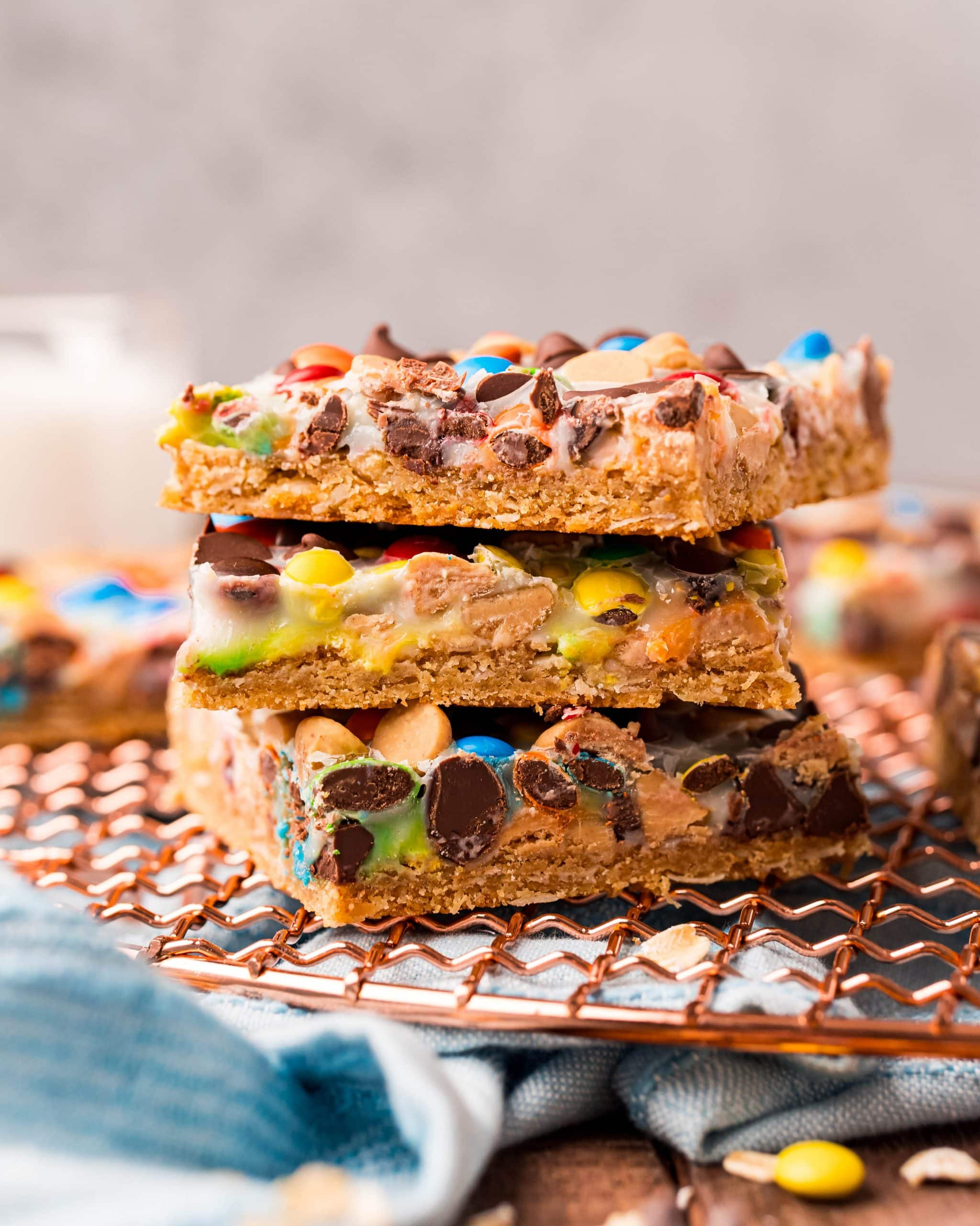 A stack of magic bars with m&ms and chocolate chips showing through the white sweetened condensed milk on top.