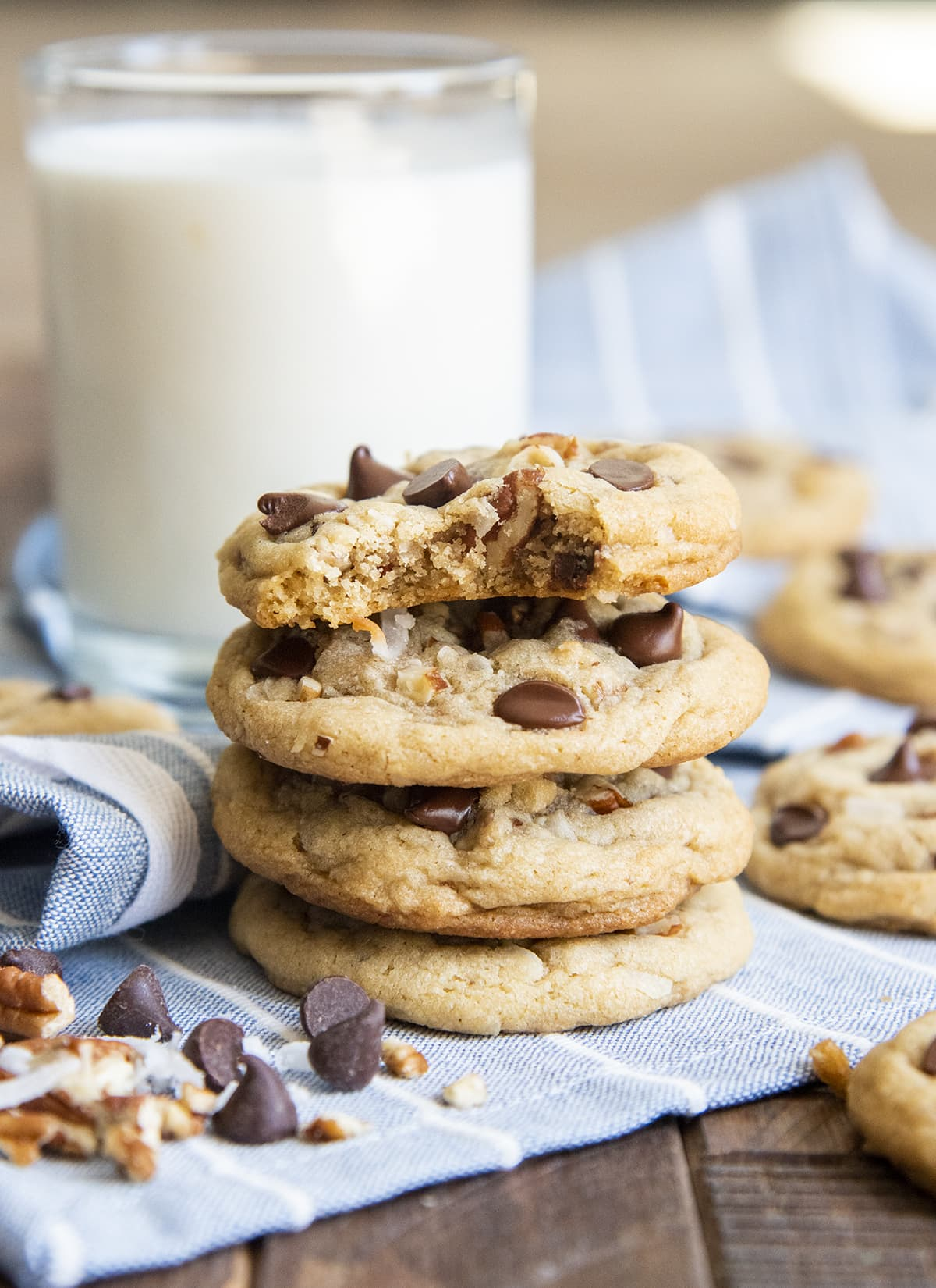 A stack of 4 drop style cookies with chocolate chips, pecans, and shredded coconut. The top cookie has a bite taken out of it.