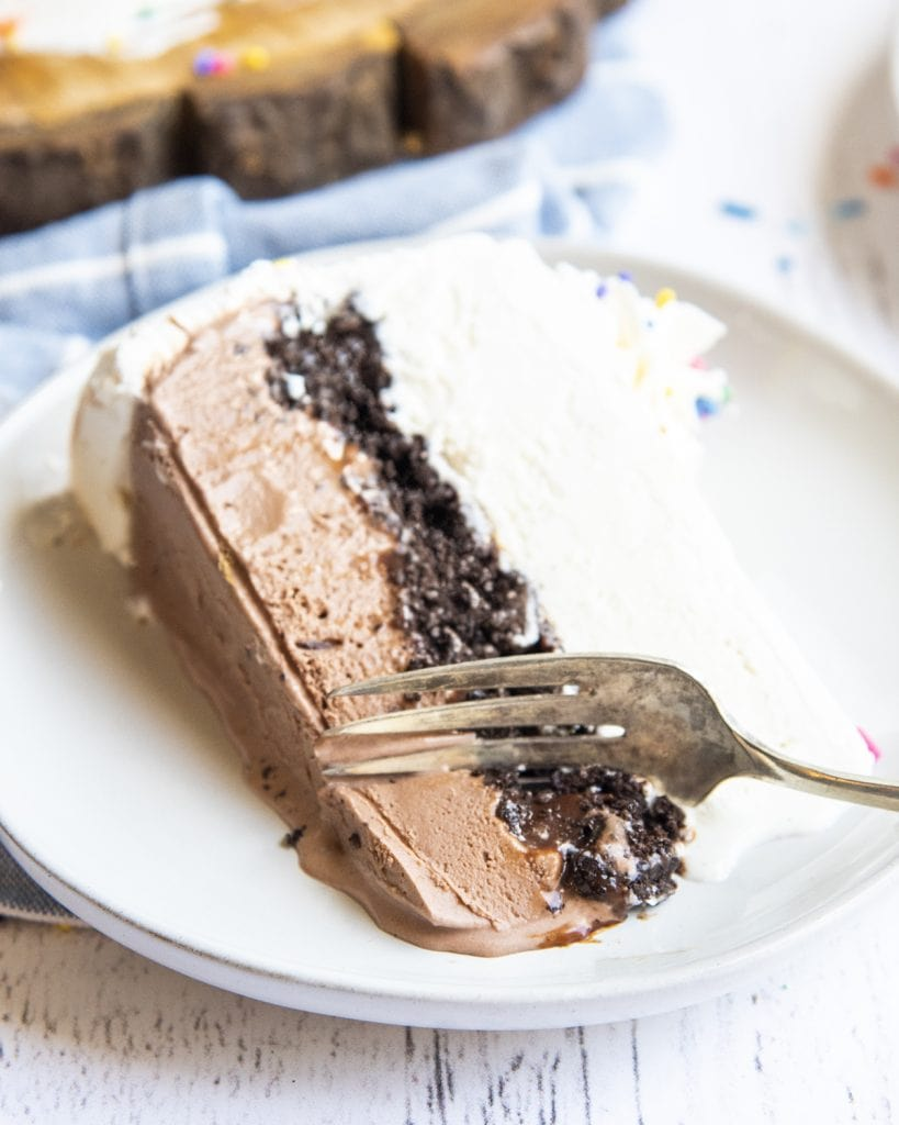 A piece of ice cream cake on a plate, with a fork cutting into the chocolate ice cream at the bottom.