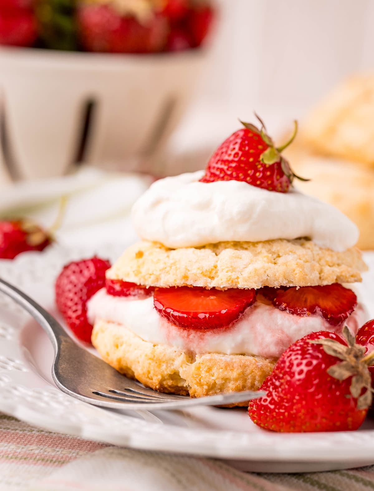 A biscuit strawberry shortcake layered with whipped cream and sliced strawberries on a white plate.