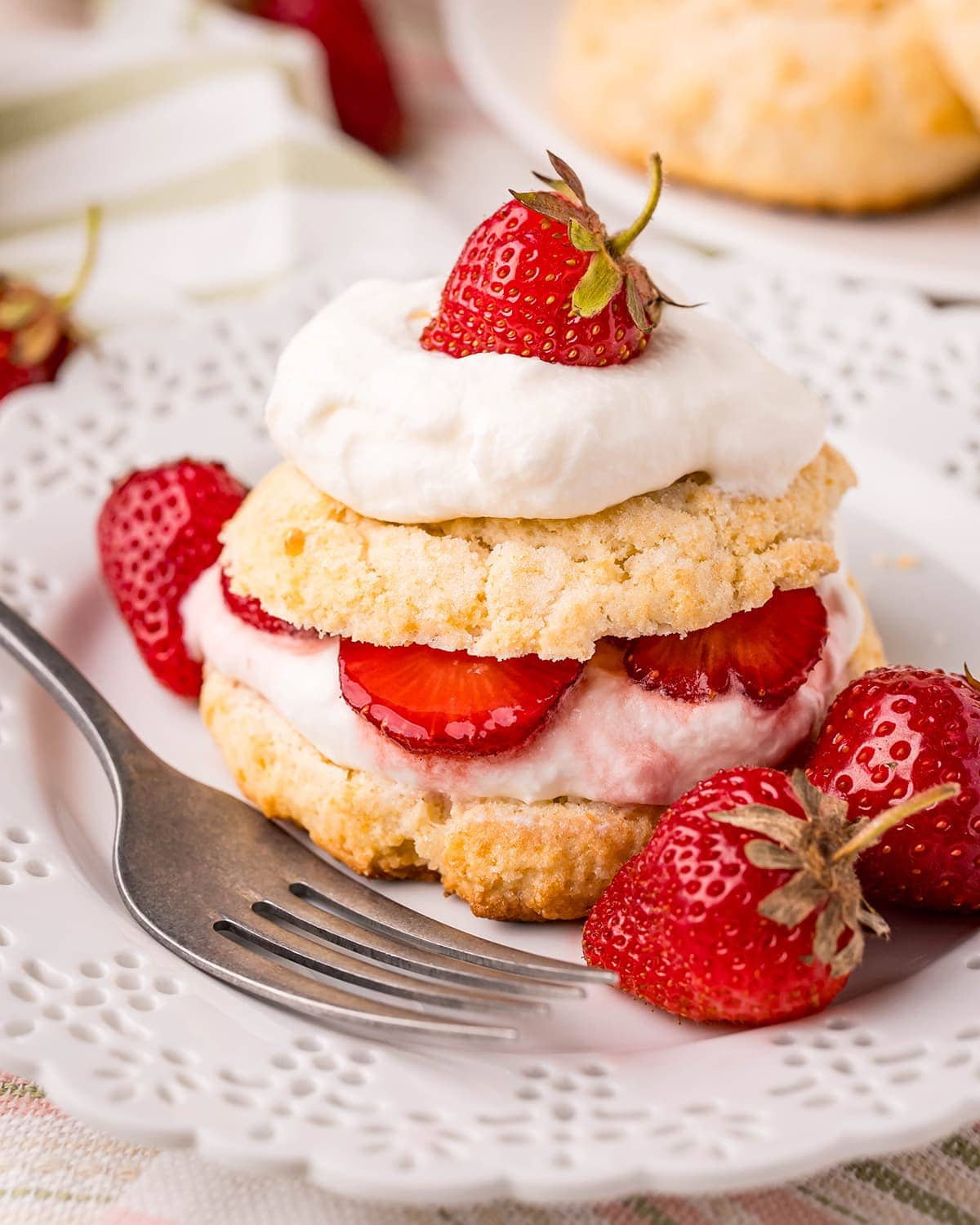 A strawberry shortcake on a white plate. The biscuit is cut in half with whipped cream, and strawberries inside, then the second half of the biscuit, and more whipped cream and a strawberry on top.