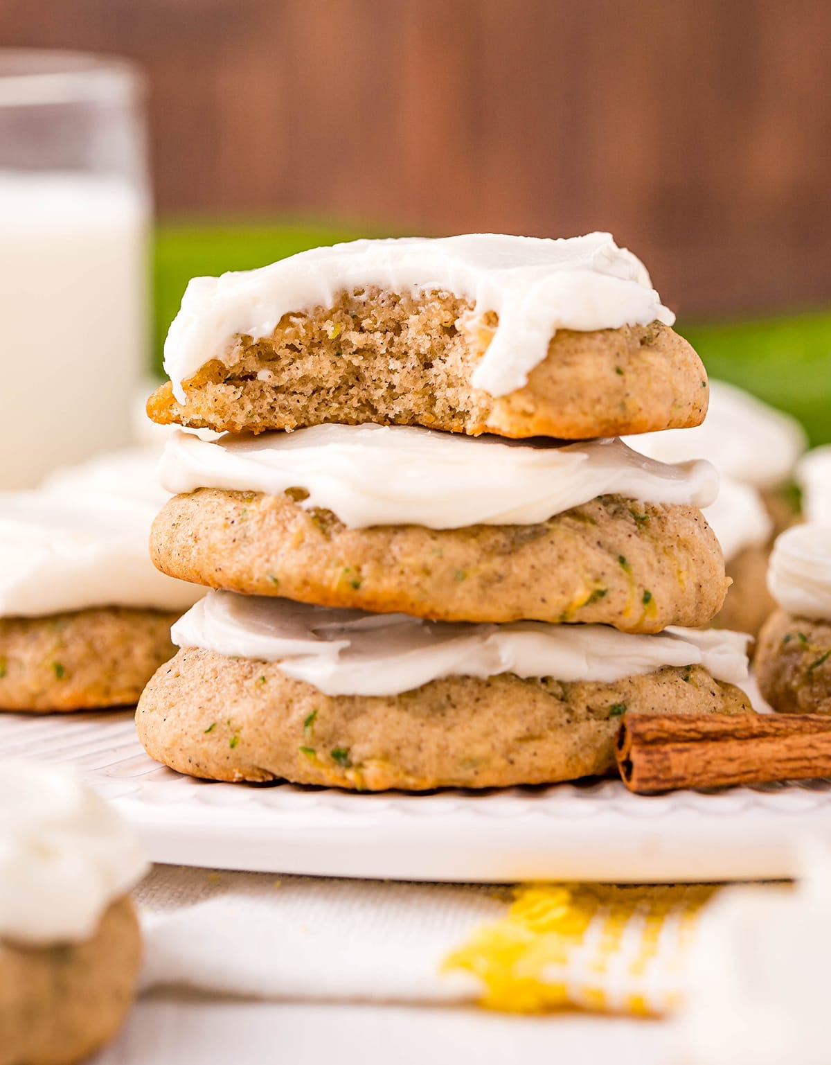 A stack of three zucchini cookies, and the top cookie has a bite out of it. The cookies are topped with cream cheese frosting.