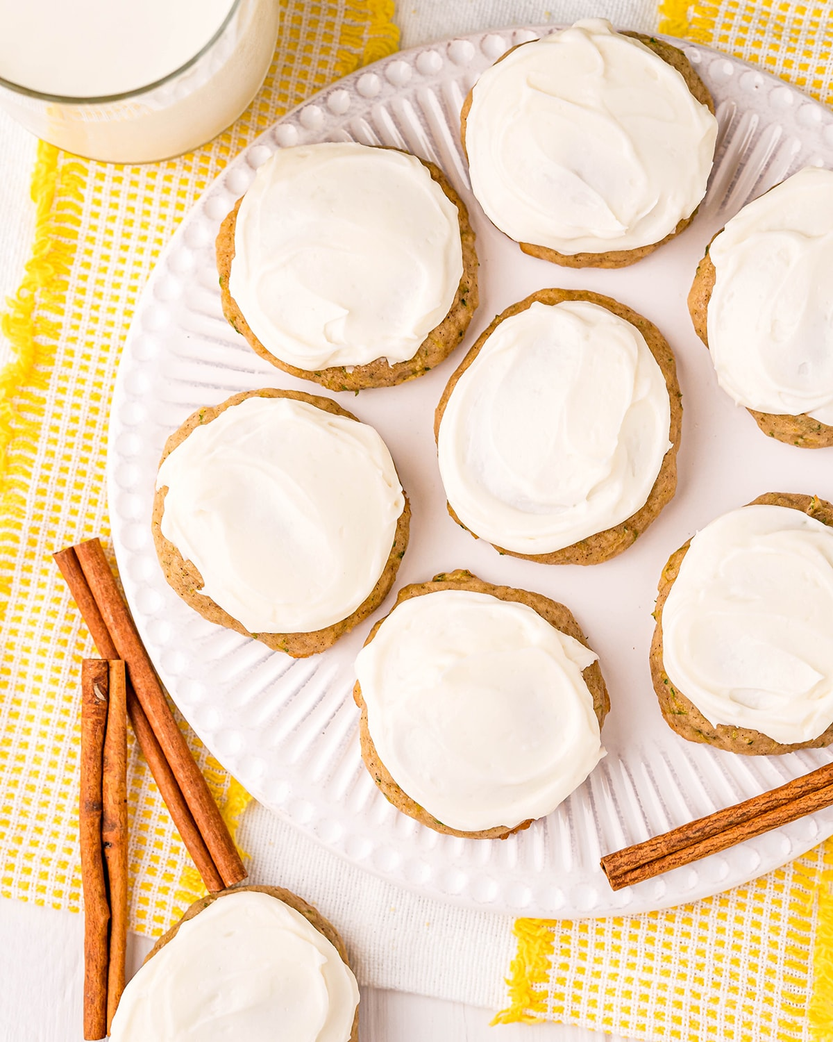 An overhead shot of a plate of cookies, topped with a white cream cheese frosting.