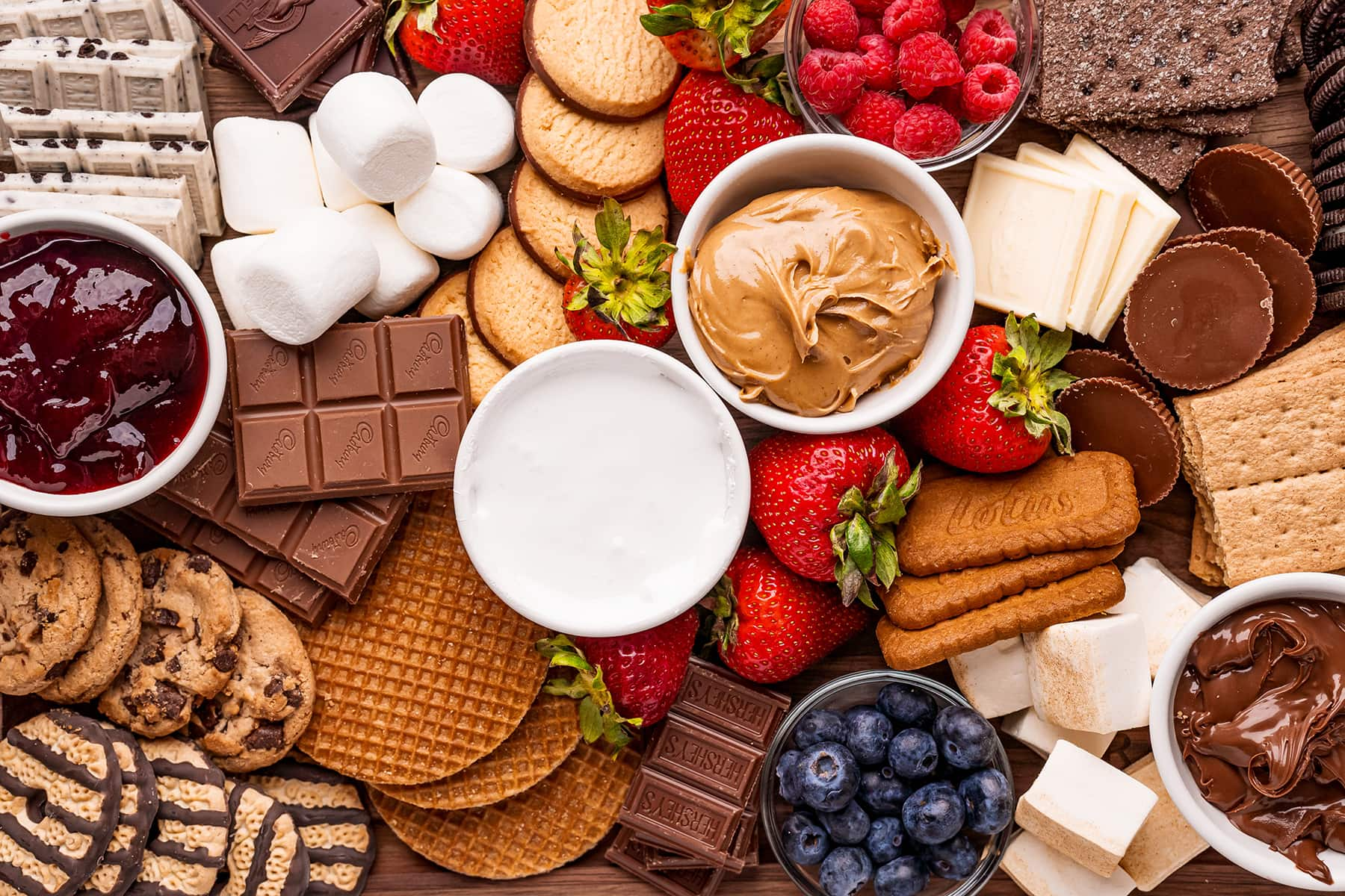 A s'mores board full of cookie choices, fresh berries, chocolate and dips to make a variety of s'mores.