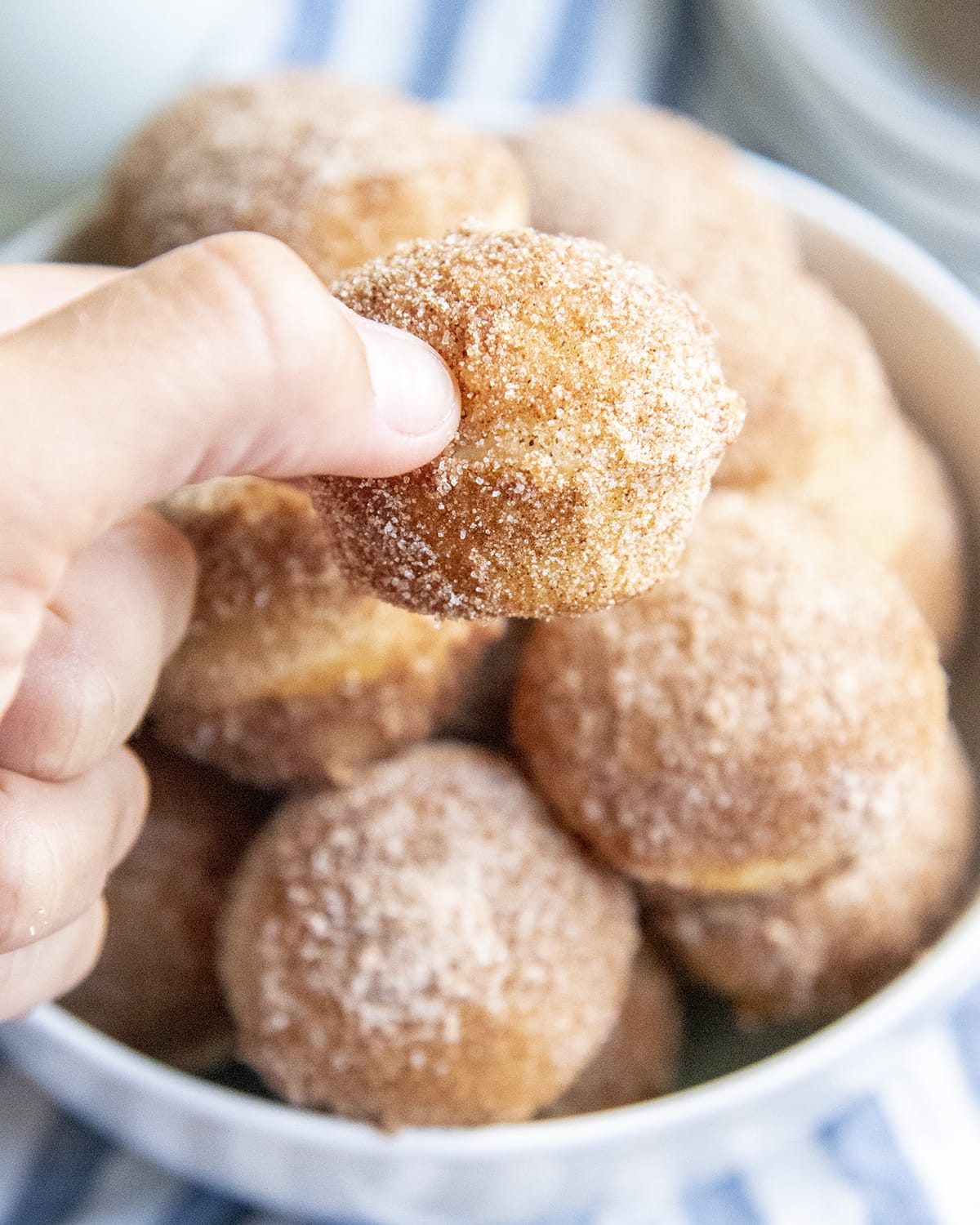 A hand holding a mini cinnamon sugar muffin above a bowl of them.