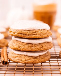 A stack of three cream cheese frosted pumpkin cookies.