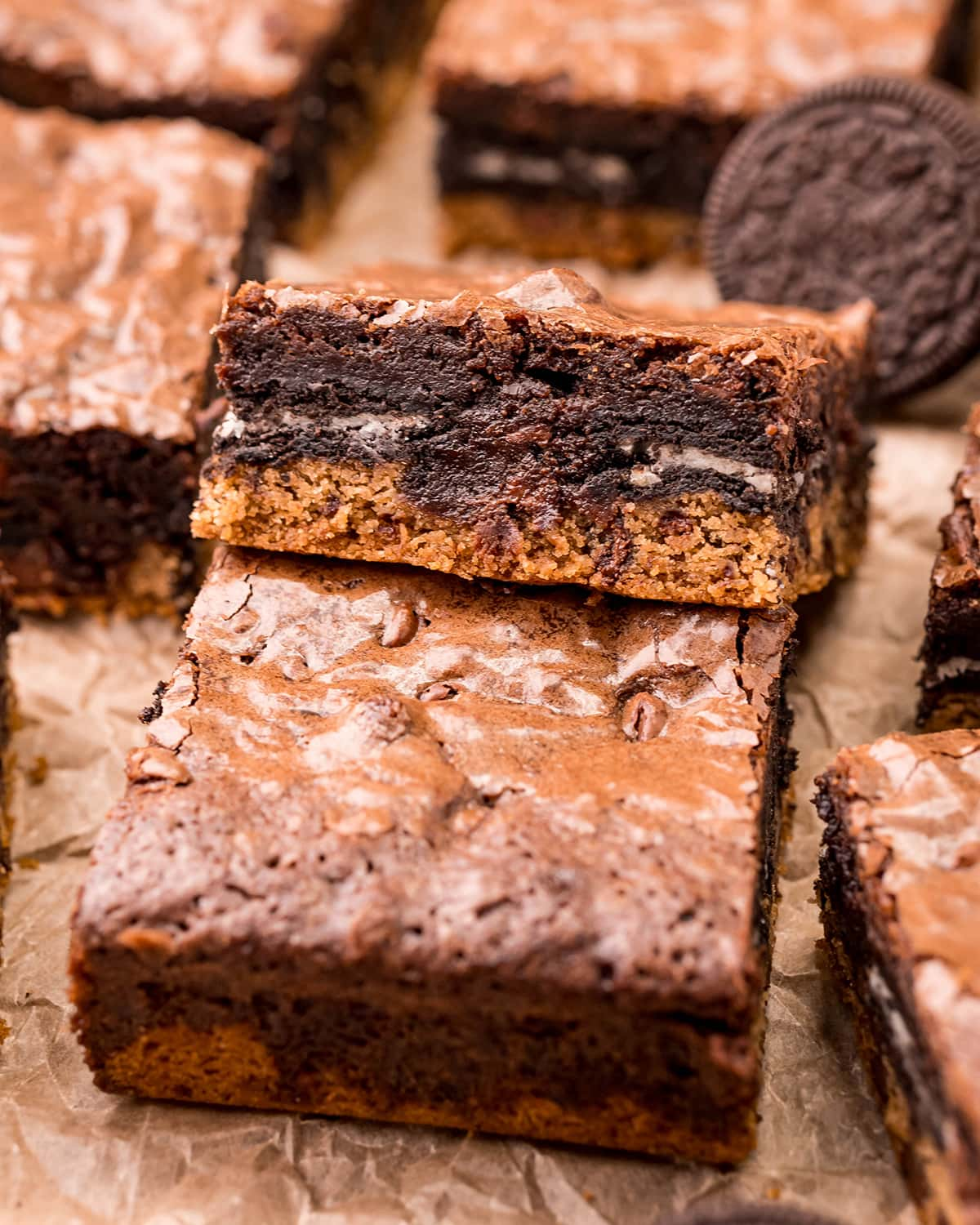 A cookie bar with chocolate chip cookie, an Oreo, and brownie on top.
