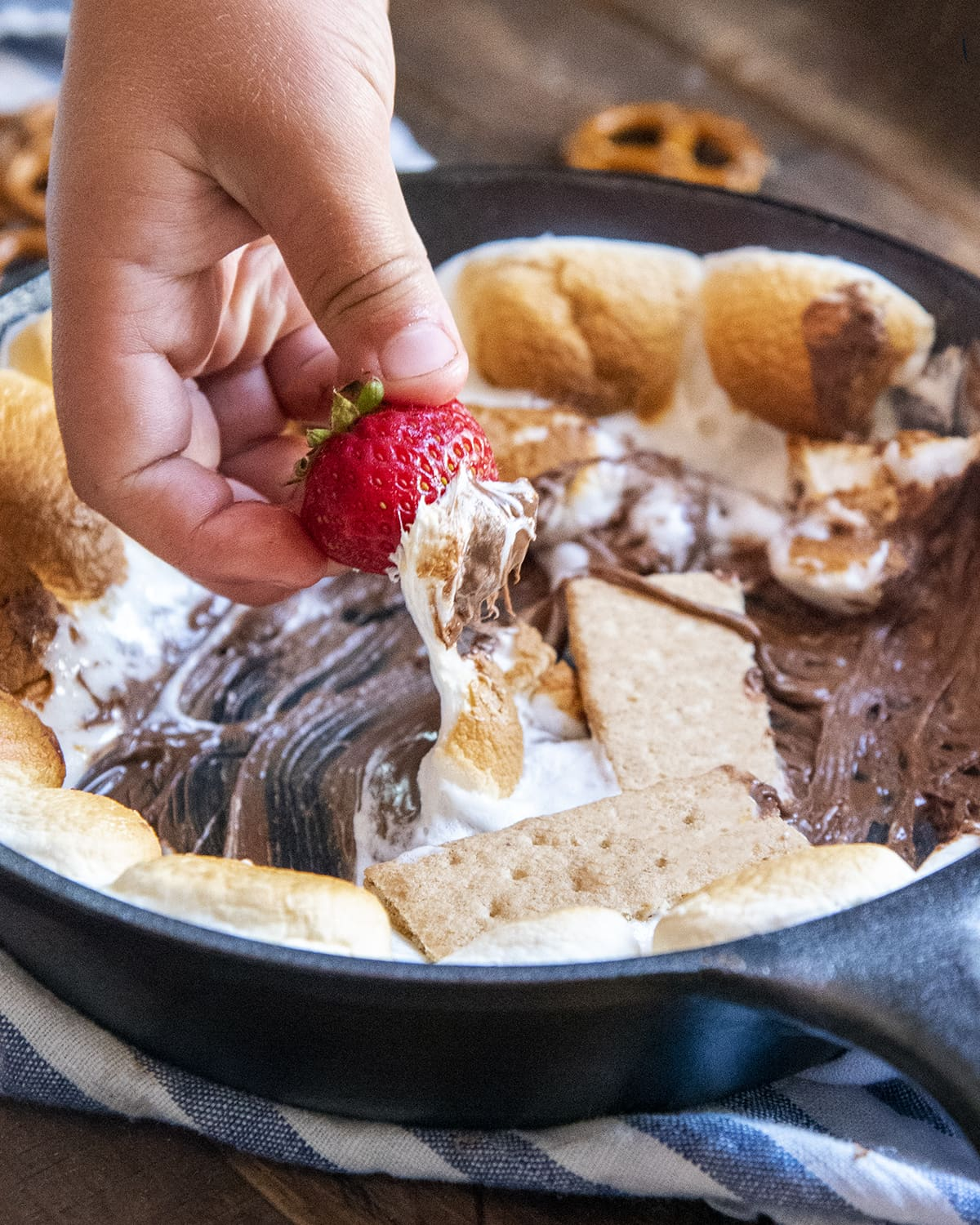 A hand dipping a strawberry into a pan of s'mores dip.