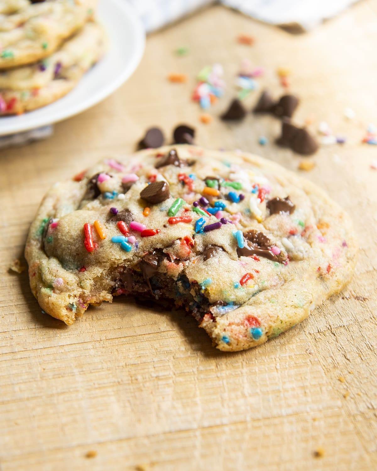 A giant chocolate chip cookie with sprinkles, with a bite taken out of it.