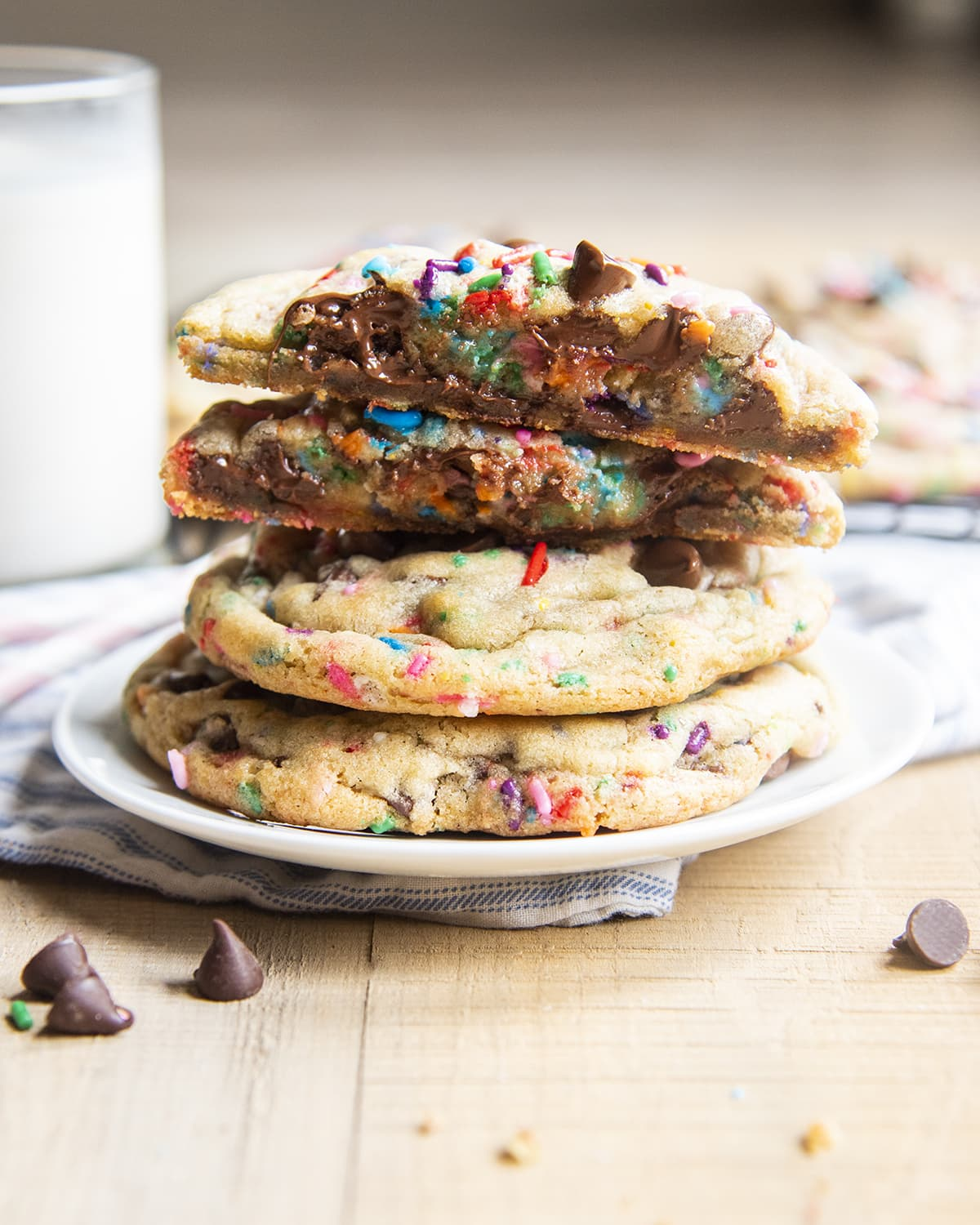 A plate stacked with funfetti chocolate chip cookies. The top is cut in half showing the melty chocolate.