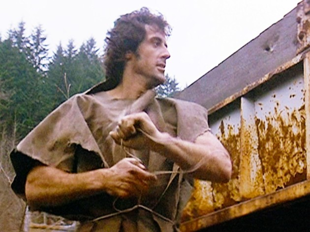 Sylvester Stallone as John Rambo fashions a poncho out of found wire and stiff canvas.