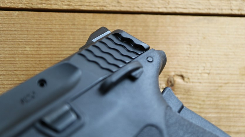"Smith & Wesson has been updating and upgrading their lineup over the last year. The M&P 2.0 series quieted previous complaints about texture and trigger. We showed you the new Shield 2.0 in November. The Bodyguard hadn't been updated and fans of Browning's .380 ACP began to feel left out. Smith & Wesson heard those cries and has released a handgun that seems perfectly modeled for the non-operator types. Winged slide of the 380 Shield EZ The .380 Shield EZ is aptly named. The pistol has been made easy to operate. Starting with the largest concern for new shooters and those with reduced strength is the slide. While styling looks just like the other M&P 2.0 models the rear of the slide has subtle wings to aid in sling-shot style racking. The action follows the standard Browning locking system which is a rare find for the caliber. Thanks to the locking system the recoil spring is soft enough that I was able to rack the gun with a finger! I don't advocate doing that with a loaded gun, but tried it as a test to just how easy the gun is to rack. The external safety is easy to engage or disengage from either side. The grip safety threw the internet into a frenzy, but deactivation is easy and it serves as simple insurance for those who might carry the gun in a purse or bag. Another interesting feature is in the two included magazines. Clearly numbered magazines with thumb assist. The magazines feature a thumb knob like one might find on a .22. While not the most comfortable thing to push on, it does serve to assist in loading. The slide release/lock also feels to be more pronounced than normal. As stated earlier everything about the 380 Shield EZ is easy! The video above provides some more details on the gun. One more fun note: The 380 Shield EZ is hammer-fired! An internal hammer eliminates any of the negatives about hammer-fired guns and still provides that nice and clean break that we all love about the action. No mush from a striker, no risk of lint or filth preventing the hammer from striking. See the video for how Smith & Wesson managed to fit that system into this new design. For those of you who love to look at numbers, the specifications below are directly from the 380 Shield EZ product page. SKU: 11663 Model: M&P® 380 SHIELD™ EZ™ Manual Thumb Safety Caliber: .380 Auto Capacity: 8+1 Barrel Length: 3.675"" / 9.3 cm Overall Length: 6.7"" Front Sight: White Dot Rear Sight: Adjustable White Dot Action: Internal Hammer Fired Grip: Polymer Weight: 18.5 oz / 524.5g Barrel Material: Stainless Steel - Armornite® Finish Slide Material: Stainless Steel - Armornite® Finish Frame Material: Polymer Purpose: Concealed Carry, Home Protection, Personal Protection"