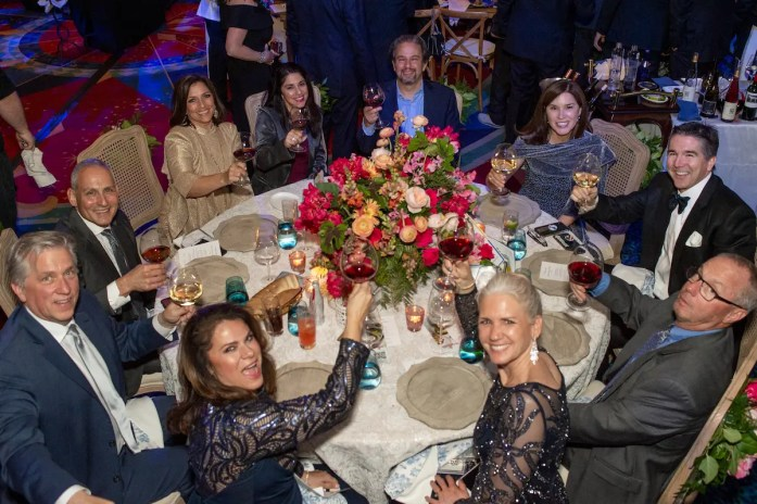 Happy dining participants raise a toast from one of 45 lavish tables at OC Chef's Table in Disneyland® Hotel's largest ballroom.