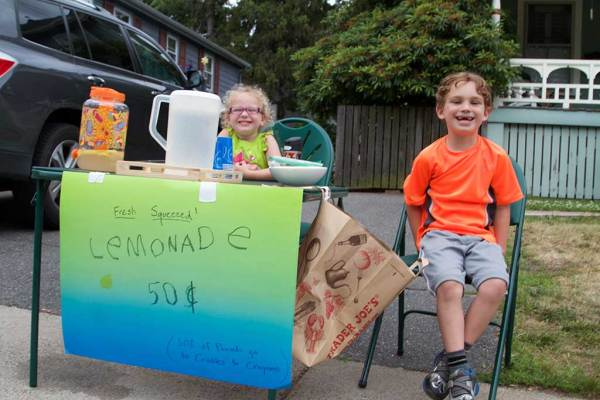 THREE-YEAR-OLD Sophia and 6-year-old Jackson Cormier were all smiles while selling lemonade to thirsty Grove Street residents this week. Proceeds from the lemonade stand were donated to Cradles to Crayons. (Donna Larsson Photo)