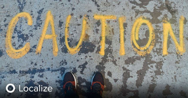 """Image: """"Caution"""" spray painted on cement in yellow paint. Description: Localization Services Mitigate the Dangers of Automated Translation"""