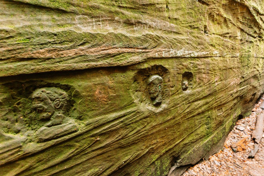 Petroglyph faces in moss covered rocks