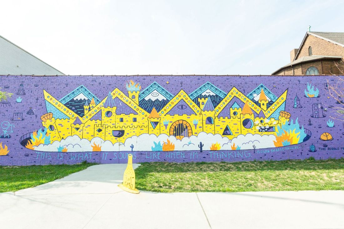 Mural of colorful characters on brick wall