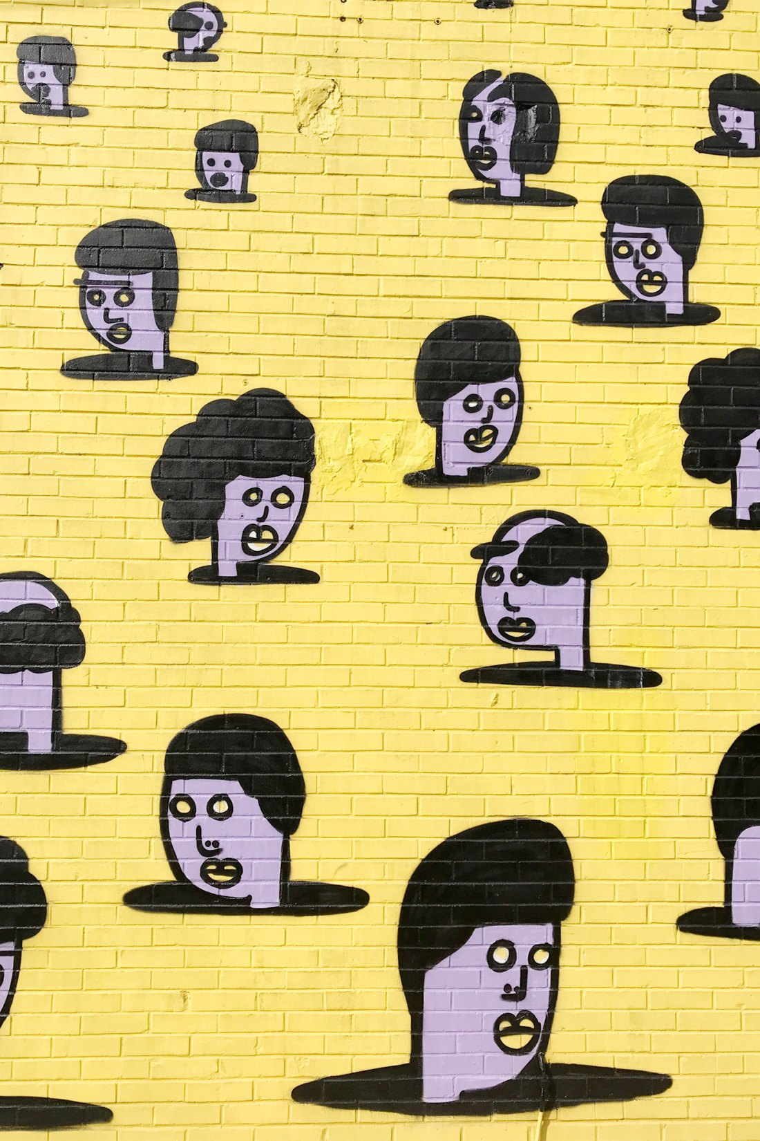 Mural of faces painted on bright yellow wall