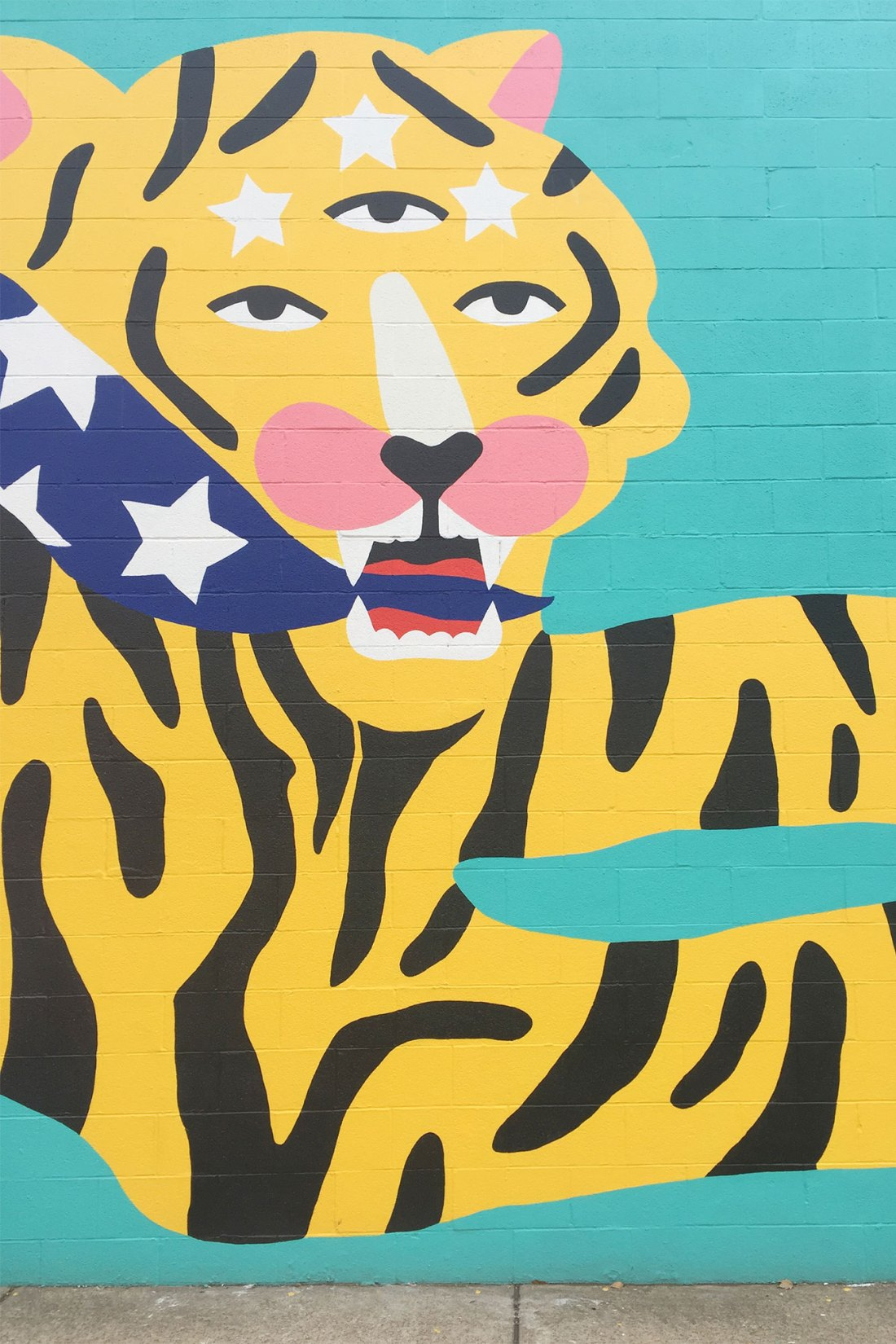 Mural of a tiger chasing a bird on side of building