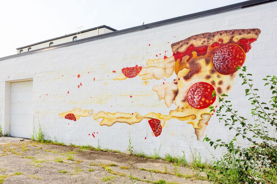 Mural of pizza on side of wall