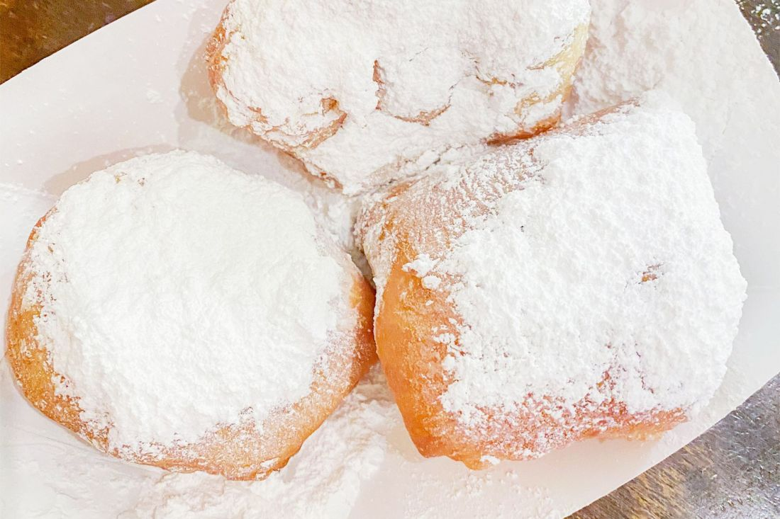 Puffed donuts covered in powdered sugar in New Orleans